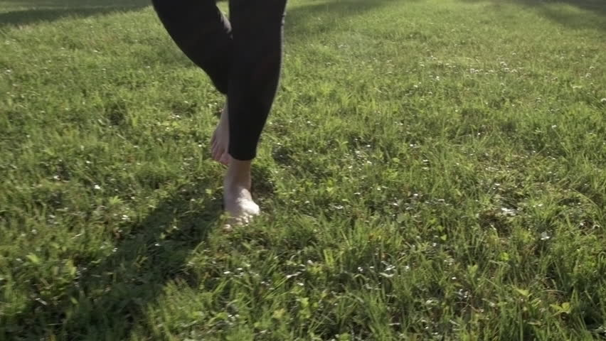 Steadicam shot of young woman walking barefoot on grass toward the camera. Backlight with the sun behind her. Natural look. With model release. | Shutterstock HD Video #18651629