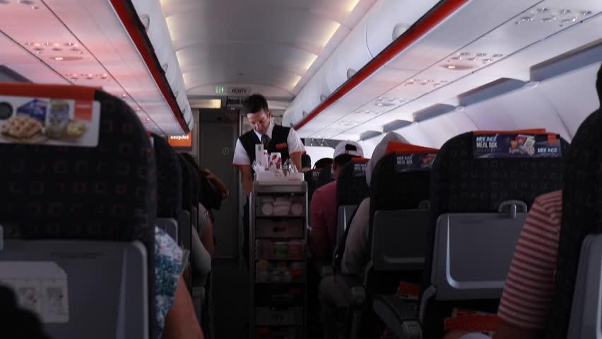 Barcelona, Spain - Circa June 2016- Flight attendant selling food on flight. Passenger buying food on flight. Plane flight interior   Shutterstock HD Video #18688151