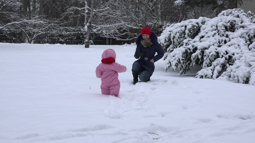 Playful mother with dummy attract baby child to walk on snow in winter. 4K | Shutterstock HD Video #18767783