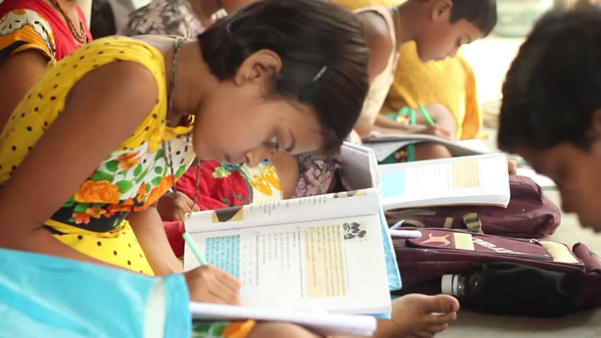 Boy and girl students diligently study in a village school in Bengal, India. Tilt shot from the side, narrow depth of field