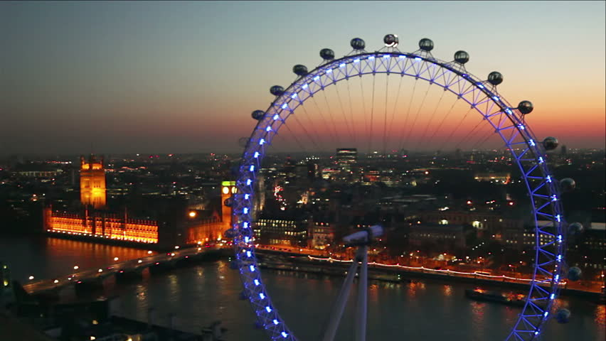 LONDON - MARCH 23: View form Shell Tower of London Eye observation wheel, Houses of Parliament and River Thames in London at sunset. Skyline of London seen at night with city lights.