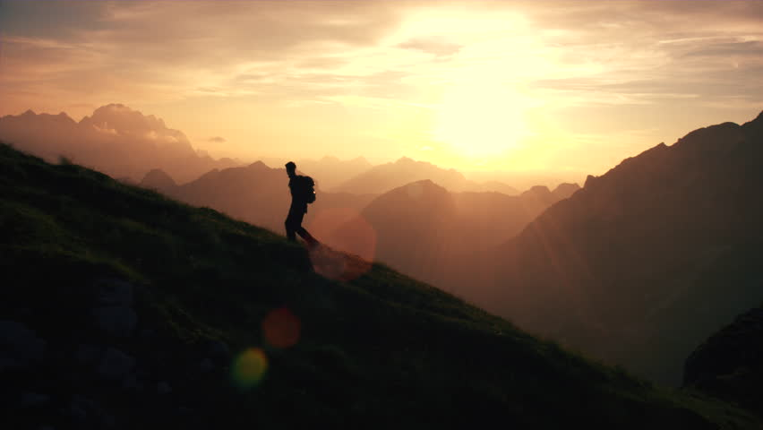 Shutterstock Aerial, edited - Epic shot of a man hiking on the edge of the mountain as a silhouette in beautiful sunset