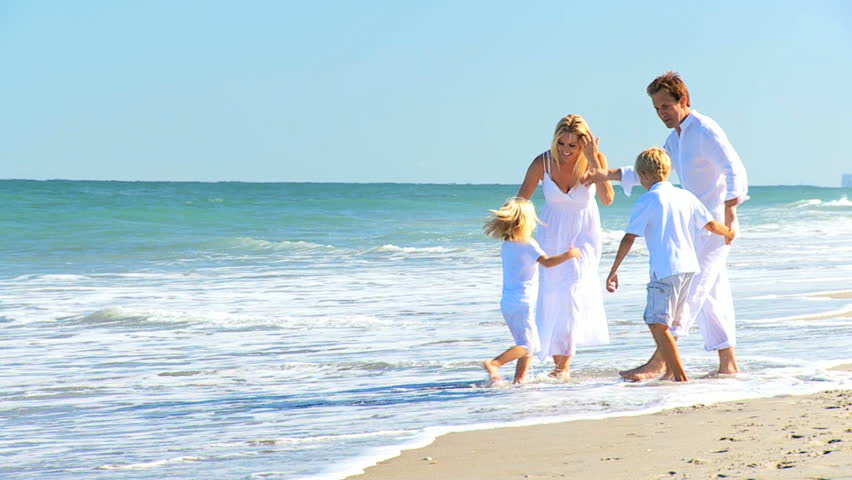 Attractive caucasian parents with their children on their back on the beach