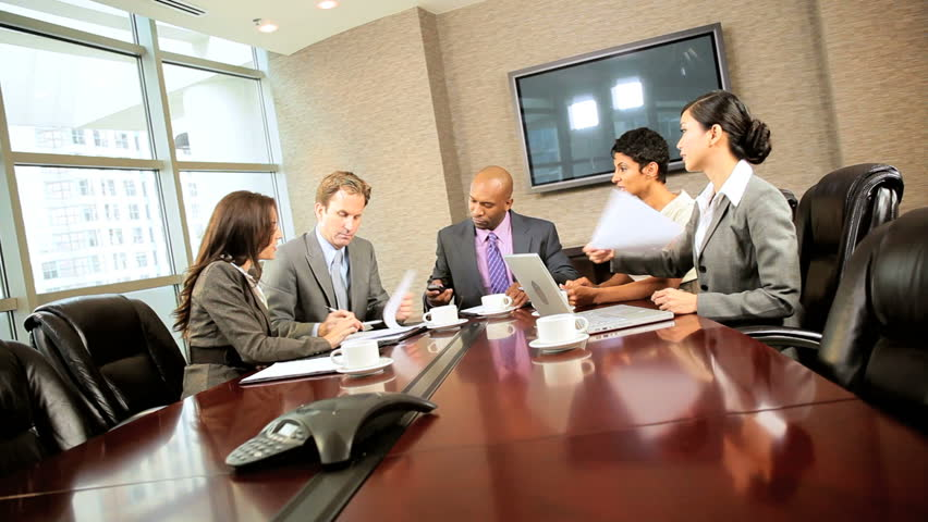 Team of five multi ethnic executives in city clothes meeting in a modern office boardroom & receiving news of success