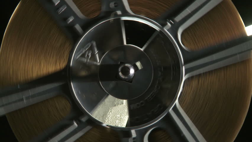 Close up of rotating 16mm film reel on projector