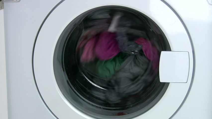 Close-up on a washing machine with clean colorful clothes - HD stock video clip
