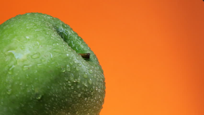 Green apple with water drops rotates on orange background - HD stock footage clip