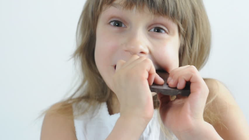 close-up portrait of a little girl eating chocolate - HD stock video clip
