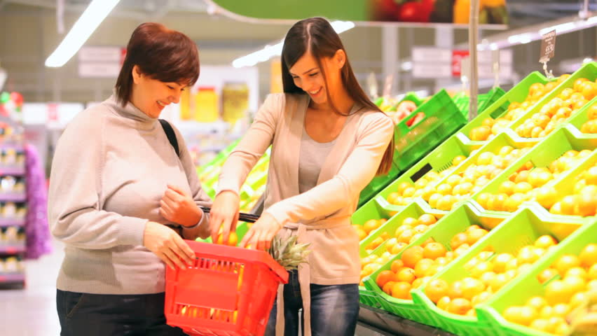 Mother and daughter choosing ripe oranges and putting them into a market basket - HD stock footage clip
