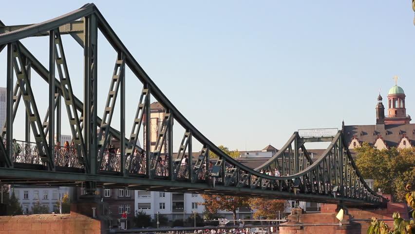 FRANKFURT, GERMANY - OCTOBER 2: People walk on the Iron Footbridge (Eiserner Steg) in Frankfurt, Germany, on October 2, 2011. The bridge was built in the 1870s to connect Sachsenhausen and Frankfurt. - HD stock video clip