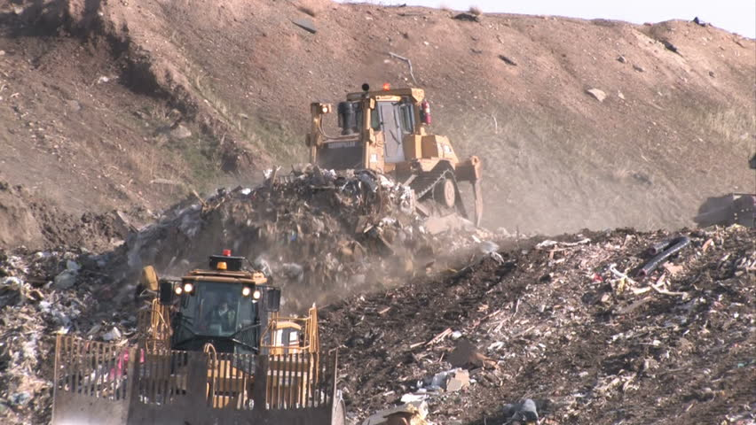 Garbage dump in Utah. Bull dozers moving garbage and trash around. A mountain of a landfill. Pollution and debris from business and residence household waste. Environmental waste non biodegradable. - HD stock footage clip