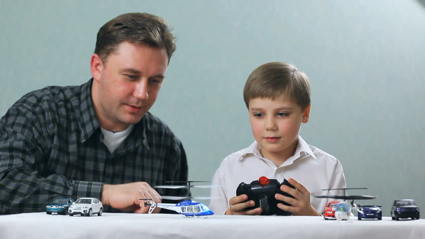 father and boy playing with a toy helicopter