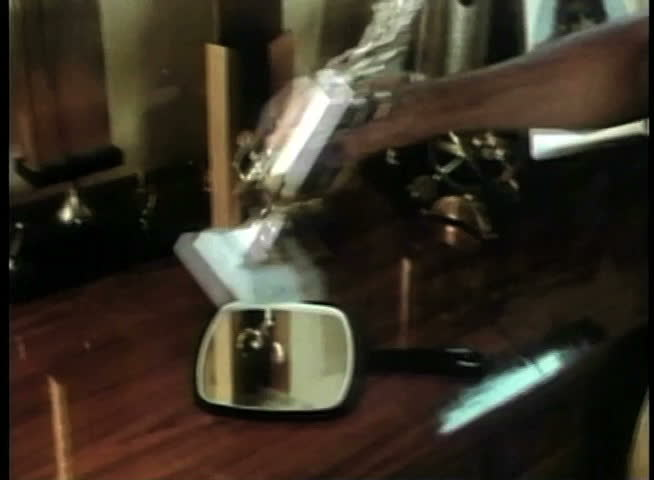 Medium shot of man picking up hand mirror on trophy table - SD stock footage clip