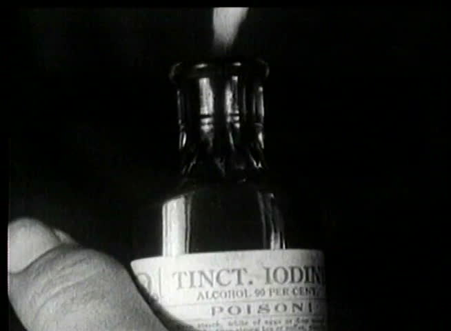 Close-up of hand dipping cotton swab into poison bottle