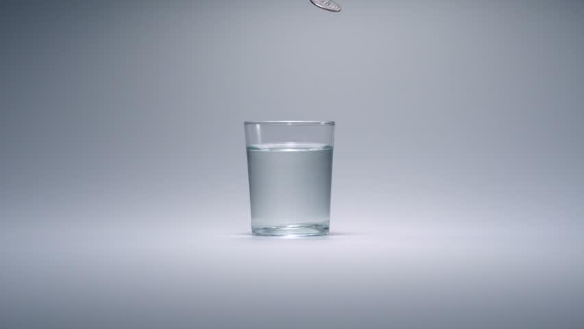 Super slo-mo quarter falling into glass of water - HD stock video clip