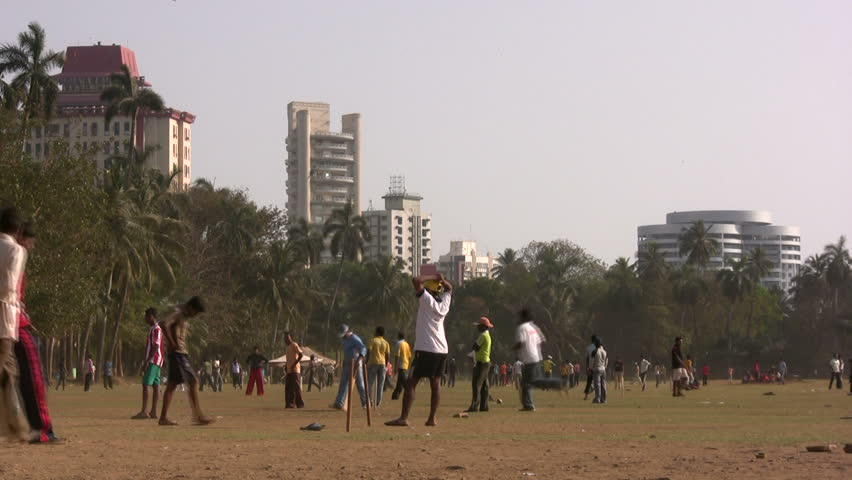 MUMBAI - 18 APRIL: People are playing cricket on a field in front of Bombay University in Mumbai - HD stock video clip