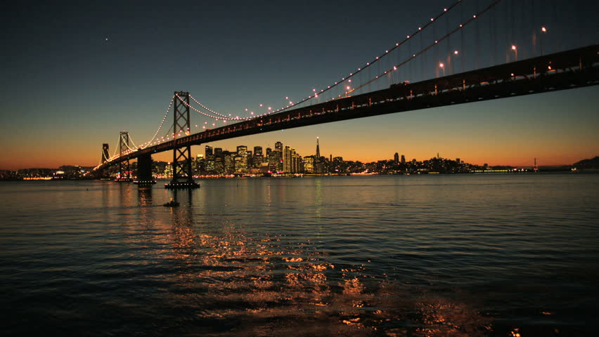 Aerial sunset low angled water view under the illuminated two levels of Oakland Bay Bridge, San Francisco, America | Shutterstock HD Video #2129051