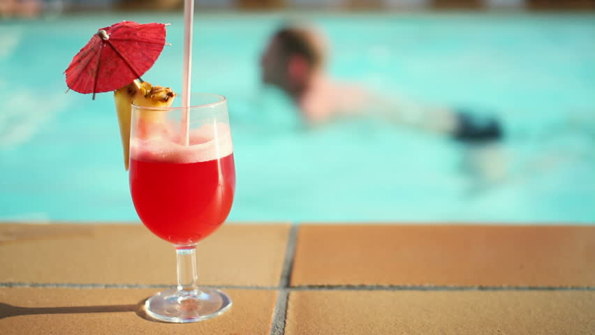 Summer drink with umbrella by the swimming pool