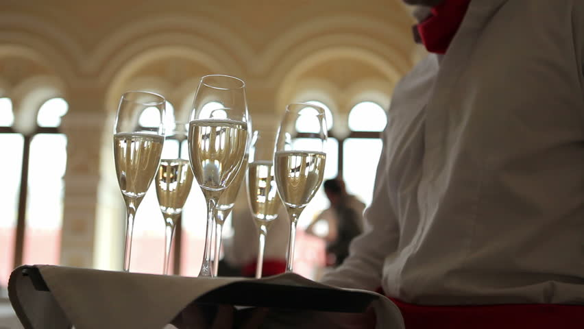 Waiter holds a tray with glasses of champagne