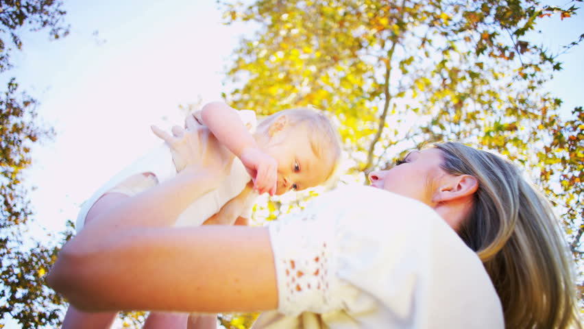 Blonde young mother and baby laughing together while playing outdoors