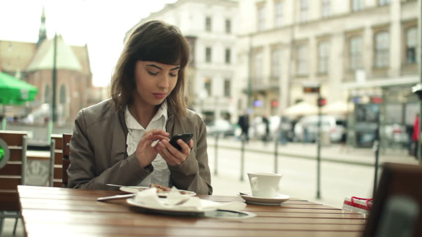 Woman using smartphone and eating in the city