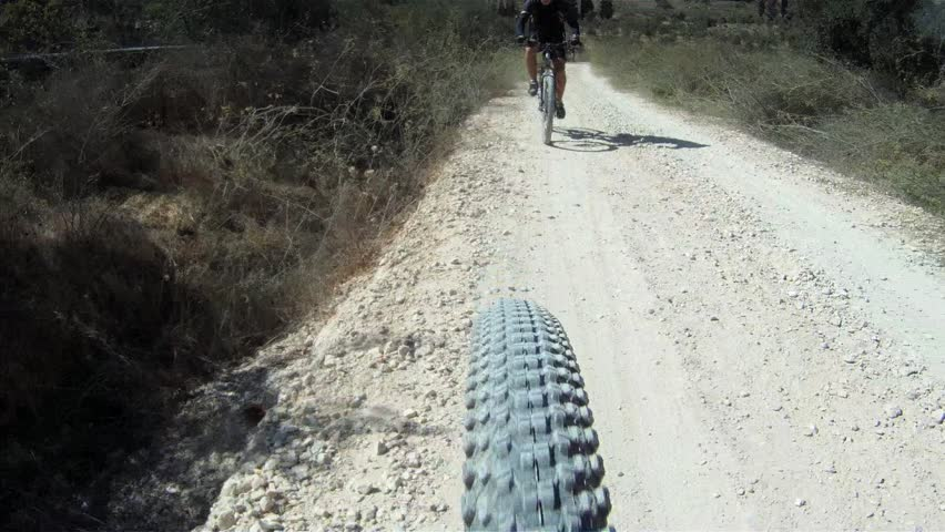 Mountain biking in israel, camera on the wheel and another person behind - HD stock footage clip