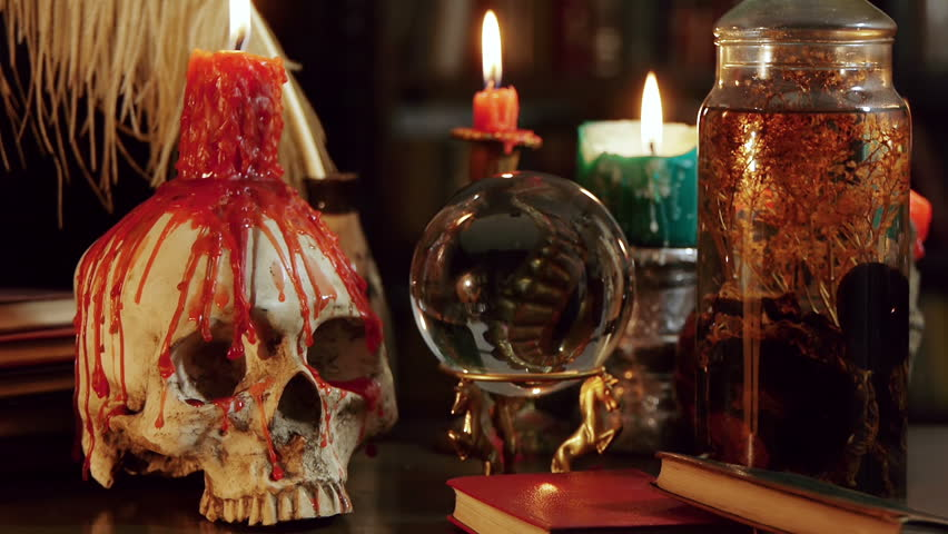 Melted Skull Candle Tilt Down (HD). Tilt Down shot of Wizard's study setup desk with a skull chandelier, candles, crystal ball, books, and other occult paraphernalia. Skull is resin replica not real.