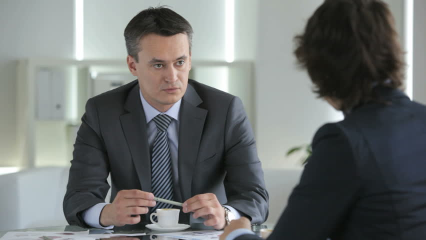 Serious businessman looking confidently and persuasively holding a job interview with an employee or having a conversation with a partner