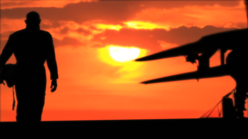 silhouette of pilot and fighter at sunset