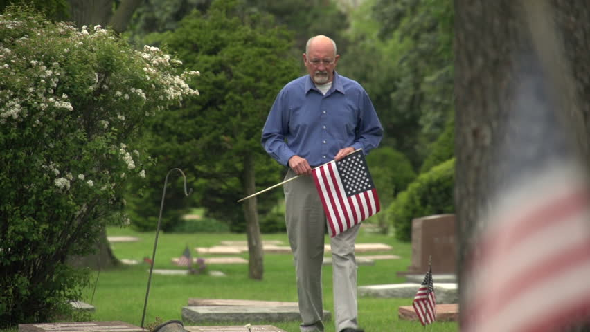 Older man walking through cemetery holding US flag - HD stock video clip