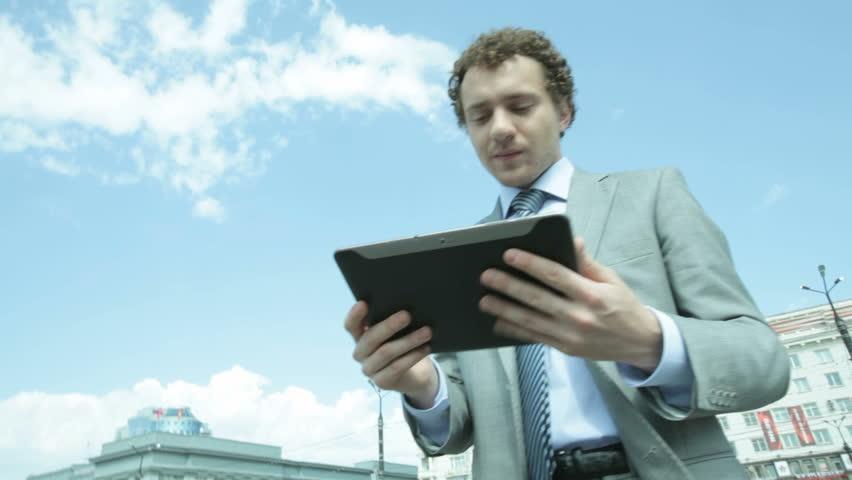 Businessman using a digital pad in urban environment, stabilized shot