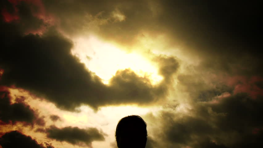 Person silhouetted raises walks up to camera, raises his hooded sweatshirt and
