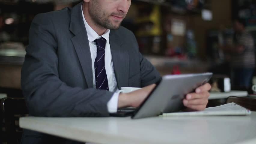 Businessman working on tablet computer in the cafe, steadicam shot
