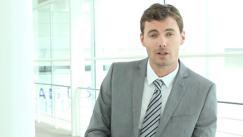 Businessman in modern building talking to camera