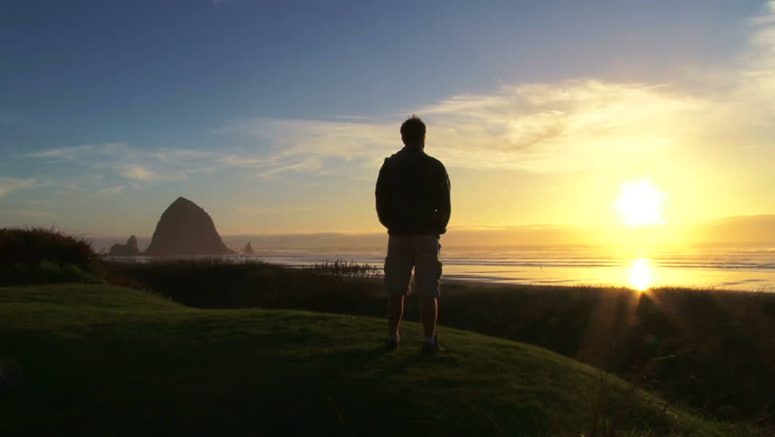 Man at Pacific Ocean near Cannon Beach looks out to sea as sun sets on beautiful day. - HD stock video clip