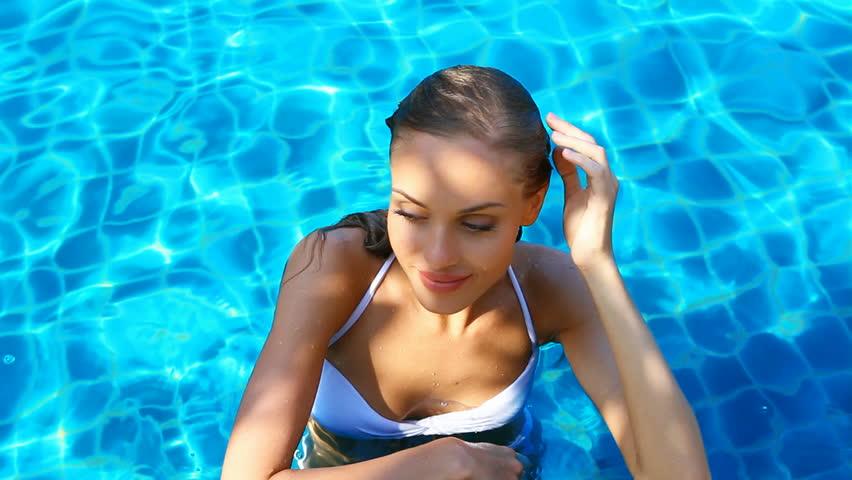 Blonde cute woman enjoys water in swimming pool