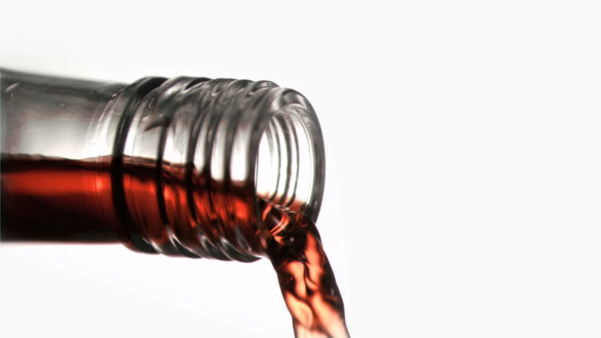 Close up,red liquid in a super slow motion flowing of the glass bottleneck against a white background - HD stock video clip
