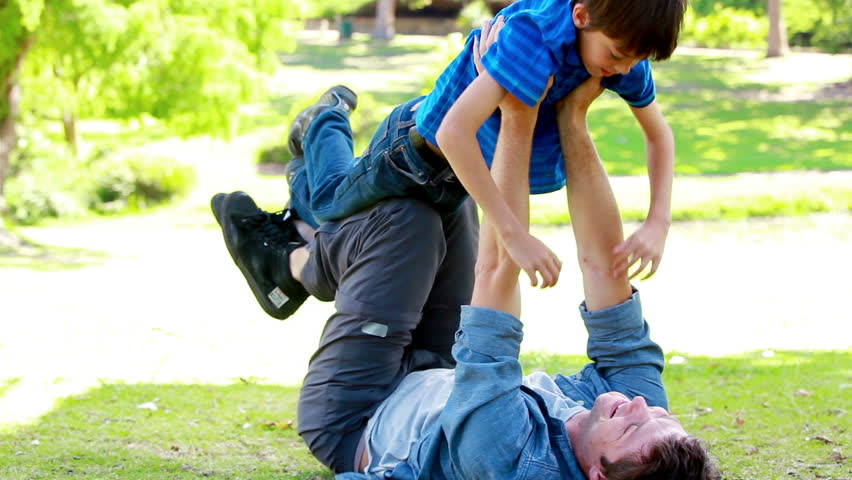Father raising his son in a park
