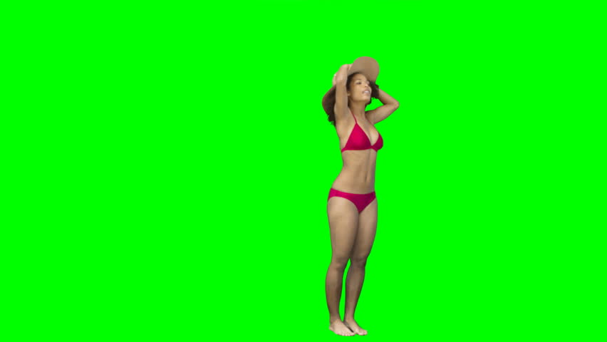 Hat falls of lady's head against a green background - HD stock video clip