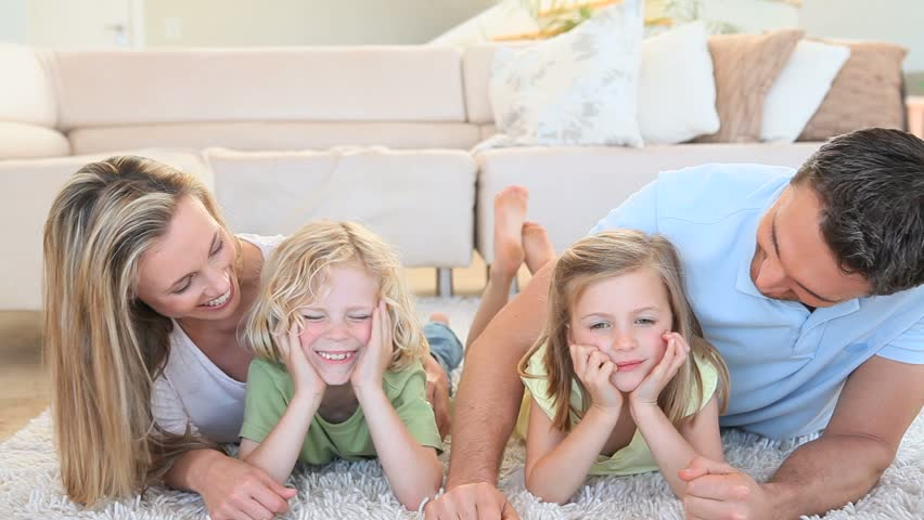 Happy family lying on the floor in the living room | Shutterstock HD Video #2390924