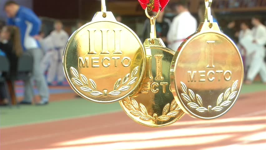 Three sport medals gleaming in the sunlight. In the background, the competition venue.   Shutterstock HD Video #24234491