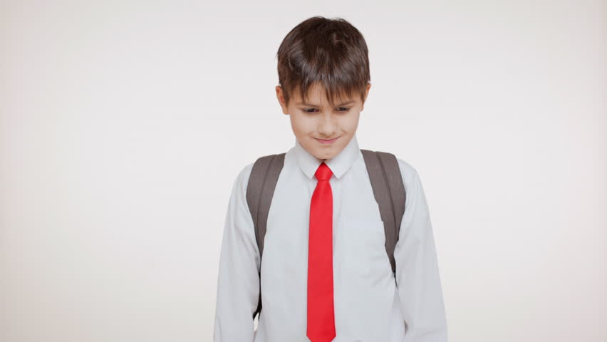 Young school kid with rucksack and red tie staying on white background at loss then smiling showing ok and yes | Shutterstock HD Video #24240557
