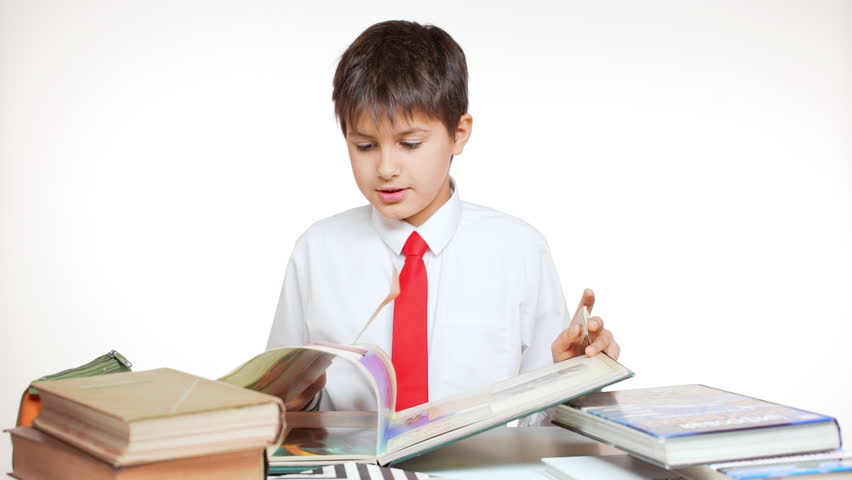 Young concentrated school kid with red tie studying atlas sitting at table with books on white background in slowmotion | Shutterstock HD Video #24255137