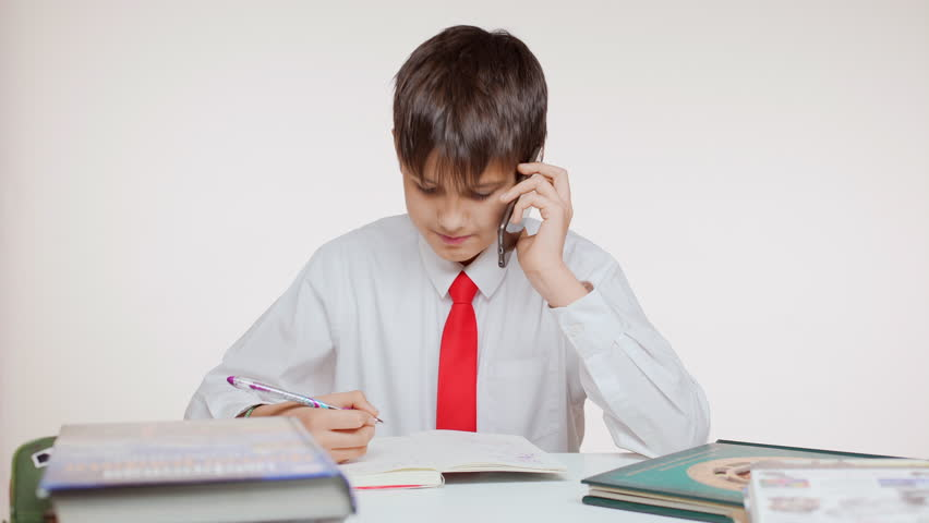 Young Caucasian school kid in red tie sitting at table writing talking on mobile phone on white background | Shutterstock HD Video #24255146