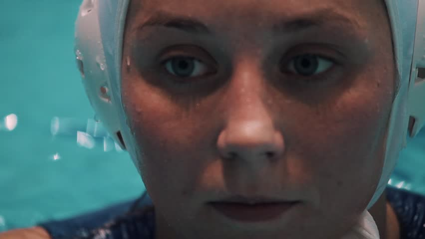 Girl water polo sport player face gray eyes in white cap blue swimsuit floating in swimming pool close up   Shutterstock HD Video #24273002