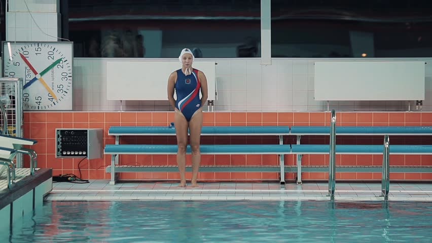 Female water polo player in white cap blue swimsuit with russian symbols dive into sports inside swim pool   Shutterstock HD Video #24273029