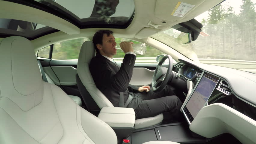 CLOSE UP: Irresponsible young businessman drinking alcohol behind the wheel while traveling in autonomous self-driving autopilot luxury electric driverless car. Male driver sipping vodka while driving | Shutterstock HD Video #24320450