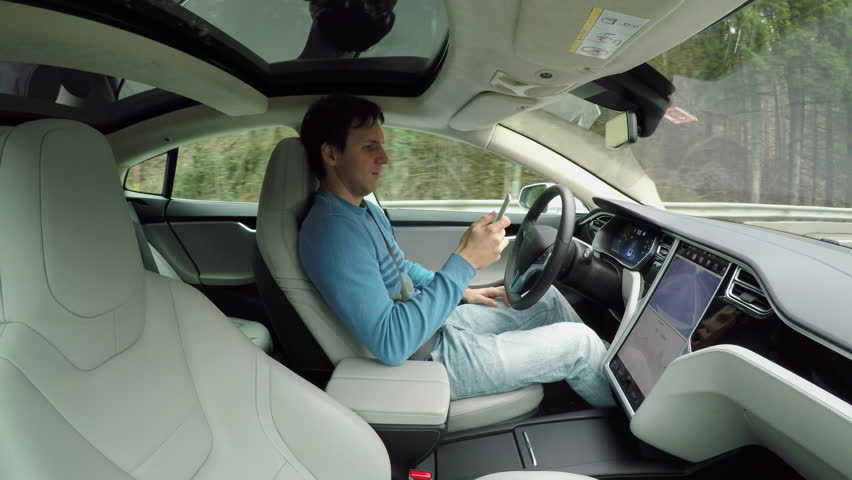 Male driver writing messages on smartphone sitting behind self-driving steering wheel in autonomous autopilot driverless electric car traveling along the countryside road. Man texting in the vehicle | Shutterstock HD Video #24320459