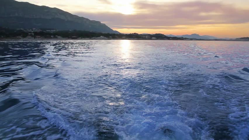 Denia sunset in Alicante Valencia Community view from a boat with prop wash - HD stock footage clip