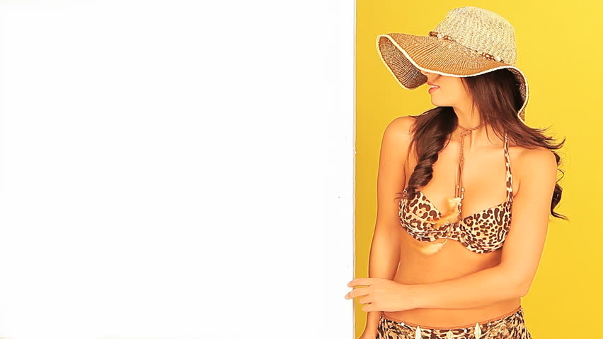 Beautiful young girl in a bikini and wide brimmed straw sun hat holding a blank white board for your text against a tropical yellow studio background - HD stock video clip